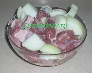 куски мяса с луком в миске